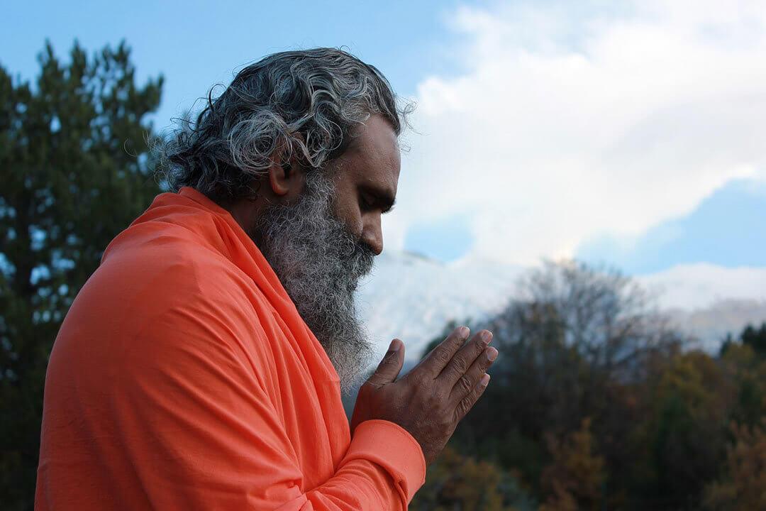 Indian Guru in orange clothes thanking
