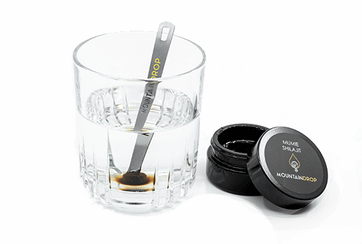 Image shows a glass of water a spoon in the water whit shilajit at the tip dissolving in to the water