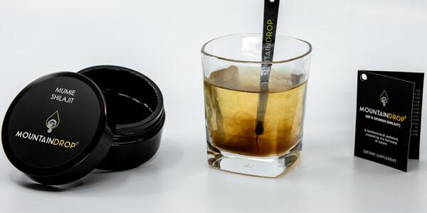 Ein Bild von Mountaindrop Shilajit, das sich in einem Glas Wasser neben einer Dose des Produkts auflöst.